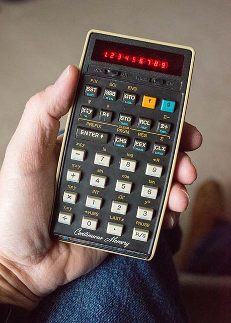 An HP-29C calculator held by a hand.