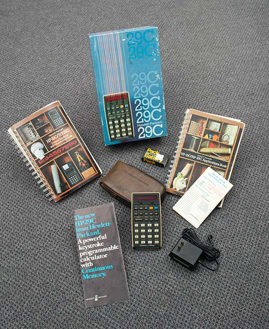 Scott's HP-29C calculator surrounded by its box, manuals, charger, and more.