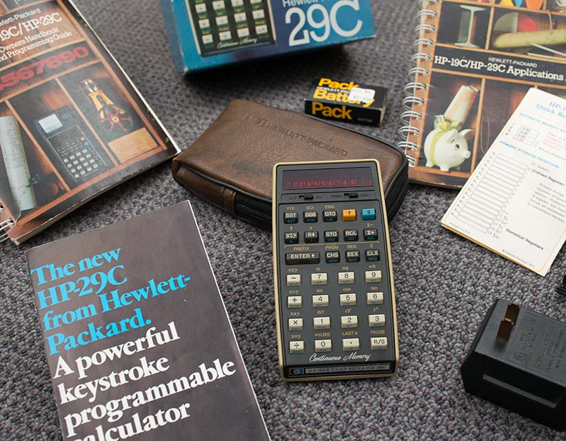 A closeup of Scott's HP-29C calculator surrounded by its box, manuals, charger, and more.